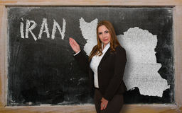 Teacher showing map of iran on blackboard. Successful, beautiful and confident young woman showing map of iran on blackboard for presentation, marketing research Royalty Free Stock Photography