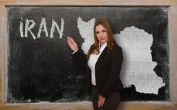 Teacher showing map of iran on blackboard Royalty Free Stock Photography