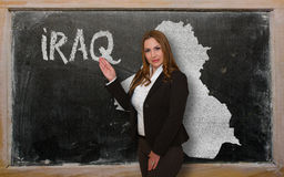 Teacher showing map of iraq on blackboard. Successful, beautiful and confident young woman showing map of iraq on blackboard for presentation, marketing research Royalty Free Stock Images