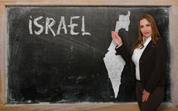 Teacher showing map of israel on blackboard. Successful, beautiful and confident young woman showing map of israel on blackboard for presentation, marketing Royalty Free Stock Images