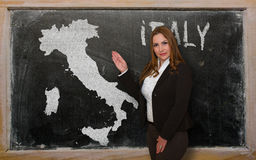 Teacher showing map of italy on blackboard. Successful, beautiful and confident young woman showing map of italy on blackboard for presentation, marketing Royalty Free Stock Photography