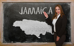 Teacher showing map of jamaica on blackboard. Successful, beautiful and confident young woman showing map of jamaica on blackboard for presentation, marketing Royalty Free Stock Photos