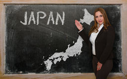Teacher showing map of japan on blackboard. Successful, beautiful and confident young woman showing map of japan on blackboard for presentation, marketing Royalty Free Stock Photography