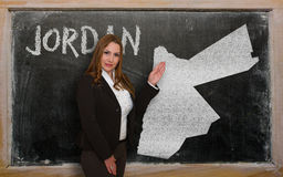 Teacher showing map of jordan on blackboard. Successful, beautiful and confident young woman showing map of jordan on blackboard for presentation, marketing Royalty Free Stock Images