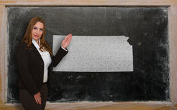 Teacher showing map of kansas on blackboard. Successful, beautiful and confident young woman showing map of kansas on blackboard for presentation, marketing Stock Image