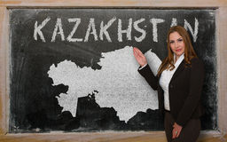 Teacher showing map of kazakhstan on blackboard. Successful, beautiful and confident young woman showing map of kazakhstan on blackboard for presentation Royalty Free Stock Image