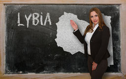 Teacher showing map of lybia on blackboard. Successful, beautiful and confident young woman showing map of lybia on blackboard for presentation, marketing Stock Image