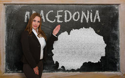 Teacher showing map of macedonia on blackboard. Successful, beautiful and confident young woman showing map of macedonia on blackboard for presentation Stock Image