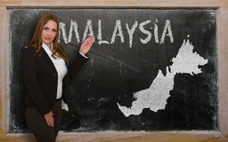 Teacher showing map of malaysia on blackboard Royalty Free Stock Photos