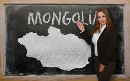 Teacher showing map of mongolia on blackboard. Successful, beautiful and confident young woman showing map of mongolia on blackboard for presentation, marketing Stock Image