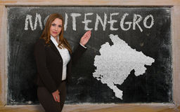 Teacher showing map of montenegro on blackboard Stock Image
