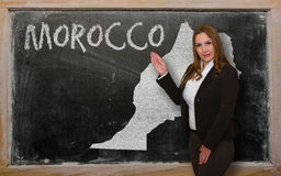 Teacher showing map of morocco on blackboard. Successful, beautiful and confident young woman showing map of morocco on blackboard for presentation, marketing Stock Images
