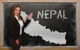 Teacher showing map of nepal on blackboard. Successful, beautiful and confident young woman showing map of nepal on blackboard for presentation, marketing Stock Image