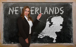 Teacher showing map of netherlands on blackboard. Successful, beautiful and confident young woman showing map of netherlands on blackboard for presentation Royalty Free Stock Photos