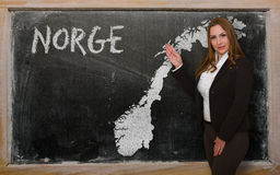 Teacher showing map of norway on blackboard Royalty Free Stock Images