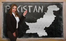 Teacher showing map of pakistan on blackboard. Successful, beautiful and confident young woman showing map of pakistan on blackboard for presentation, marketing Stock Photography