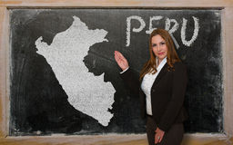 Teacher showing map of peru on blackboard. Successful, beautiful and confident young woman showing map of peru on blackboard for presentation, marketing research Stock Photos