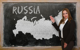Teacher showing map of russia on blackboard. Successful, beautiful and confident young woman showing map of russia on blackboard for presentation, marketing Royalty Free Stock Image