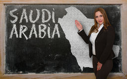 Teacher showing map of saudi arabia on blackboard. Successful, beautiful and confident young woman showing map of saudi arabia on blackboard for presentation Royalty Free Stock Photography