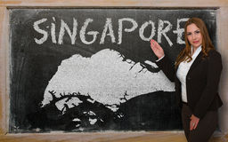Teacher showing map of singapore on blackboard. Successful, beautiful and confident young woman showing map of singapore on blackboard for presentation Stock Photos