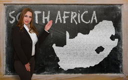 Teacher showing map of south africa on blackboard. Successful, beautiful and confident young woman showing map of south africa on blackboard for presentation Stock Image
