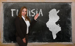 Teacher showing map of tunisia on blackboard. Successful, beautiful and confident young woman showing map of tunisia on blackboard for presentation, marketing Royalty Free Stock Photo