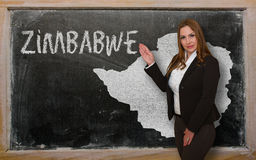 Teacher showing map of zimbabwe on blackboard. Successful, beautiful and confident young woman showing map of zimbabwe on blackboard for presentation, marketing Royalty Free Stock Photography