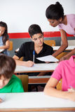 Teacher Showing Paper To University Student Stock Image