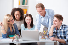 Teacher showing something his best students. During the break.  Positive and relaxed teacher having nice time with his nice young students during the break Royalty Free Stock Image