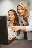 Teacher showing something on screen to student Royalty Free Stock Photography