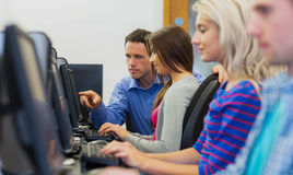 Teacher showing something on screen to student in computer room Royalty Free Stock Photos