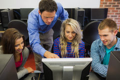 Teacher showing something on screen to students in computer room Stock Images