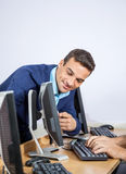 Teacher Showing Something To Senior Man On Computer In Classroom Stock Photo