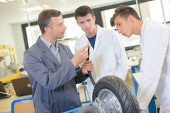 Teacher showing students adapter for inflating tyre Stock Photo