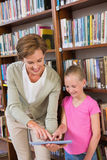Teacher showing tablet to pupil at library Royalty Free Stock Image