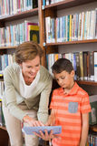 Teacher showing tablet to pupil at library Stock Image