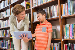 Teacher showing tablet to pupil at library Royalty Free Stock Photography