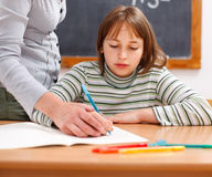 Teacher showing writing to schoolgirl Stock Photo