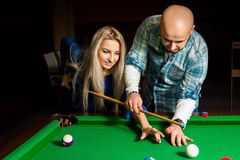 Teacher shows a girl how to play pool billiard Royalty Free Stock Photo