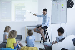 Teacher shows on an interactive whiteboard. Teacher shows students how to program on an interactive whiteboard. Modern teaching concept Royalty Free Stock Photography