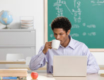 Teacher sipping coffee and working on laptop Stock Images