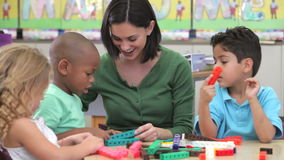 Teacher Sits With Group Of Children Using Construction Kit stock footage