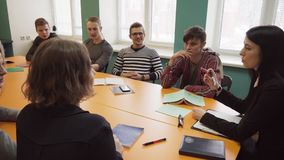 Teacher sits at a table and talks with students at university. A female teacher sits at a table and talks with students at university stock footage