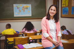 Teacher sitting behind her students Stock Photos