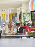 Teacher Sitting With Boy Using Laptop In Class Stock Photos
