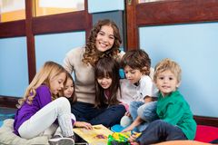 Teacher Sitting With Children On Floor Royalty Free Stock Photos