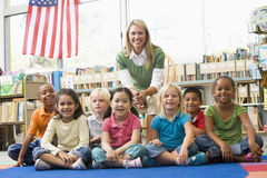 Teacher sitting with children in library. Kindergarten teacher sitting with children in library stock photo