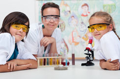 Teacher sitting at the desk with her young students Stock Images