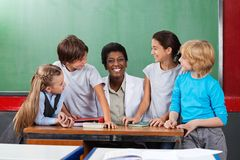 Teacher Sitting At Desk With Students At Desk. Portrait of young teacher sitting at desk with students looking at her in classroom Royalty Free Stock Photos