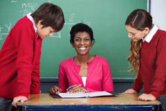 Teacher Sitting At Desk With Students. Portrait of happy young African American female teacher sitting at desk with students in classroom Stock Photos